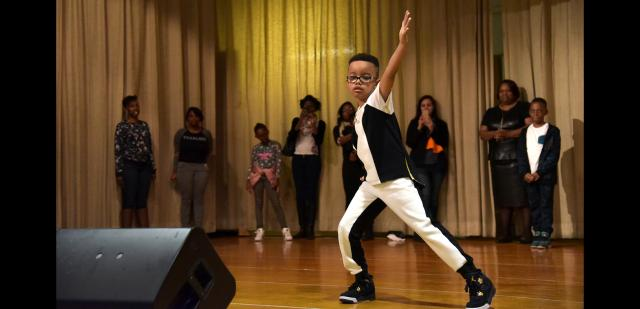 At a recent  Save Our Streets, 'Stop Shooting, Start Living'  talent show in Crown Heights, Brooklyn, Lavon Walker Jr. performs a dance tribute to his father to the music of Michael Jackson. Lavon Walker was a founding member of  S.O.S. in Crown Heights who was  fatally shot in Miami last year. More than 300 people attended the show, with a number of performances addressing the effects of gun violence and the importance of S.O.S.'s work to engage its community. (Photo courtesy of  Sina Basila.)