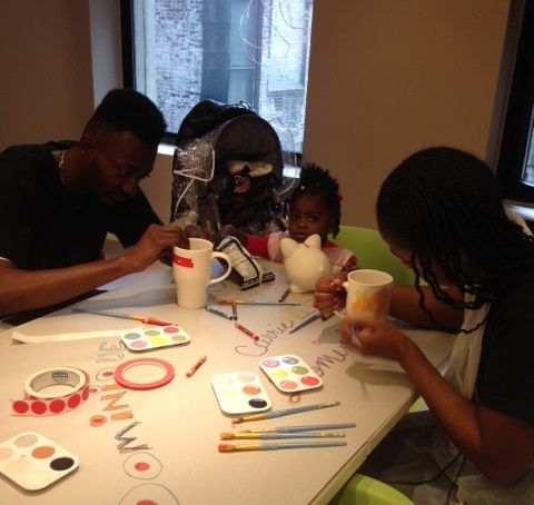 In honor of Mother's Day, participants in Midtown Community Court's UPNEXT program join an event at Making Meaning, sponsored by the Department of Youth and Community Development, which seeks to strengthen family relationships. Here, Brett Stewart (left) paints pottery with his daughter, Zatara (center) and her mother, Dominique (right). (May 15, 2014)