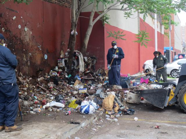 The Brownsville Community Justice Center coordinated a multi-agency cleanup with the New York City Housing Authority (NYCHA), Department of Sanitation, and New York Police Department (NYPD), clearing over six tons of trash and debris from a dump site that had been an eyesore for the Brownsville, Brooklyn community for decades. (May 29, 2014)
