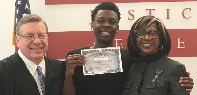 American Bar Association President Paulette Brown and Judge Alex Calabrese congratulate the young graduate Jared Chris Sumpter at his GED graduation ceremony at the Red Hook Community Justice Center this month. Chris, a Red Hook resident, is now working on internship and college applications.