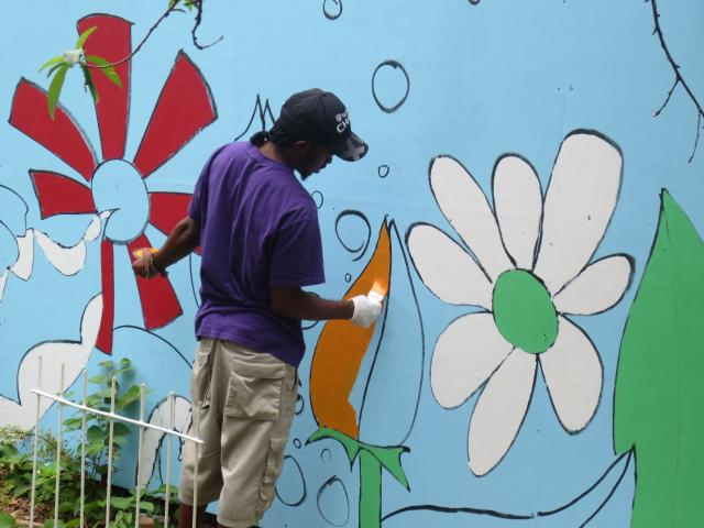 A youth works on a mural in a community garden in Brownsville, Brooklyn. This is just part of the Brownsville Community Justice Center's initiative to offer 254 young people from Brownsville paid opportunities in community restoration projects, internships, and the arts this year. (July 18, 2013)