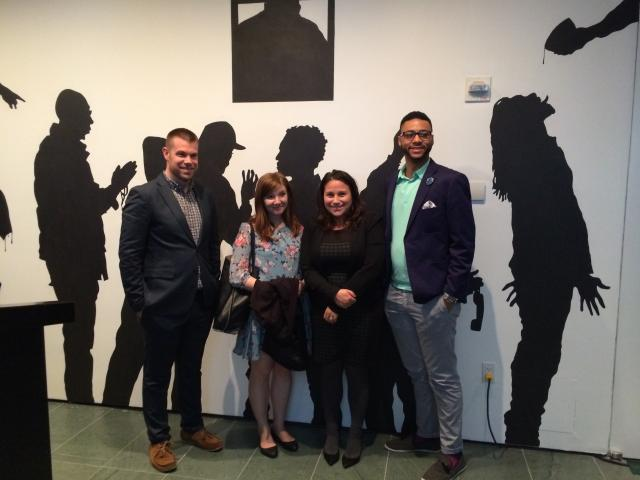 Midtown Community Court's workforce development and fatherhood program, UpNext, collaborated with MoMA educator Shellyne Rodriguez to find a place where participants could share their experiences as fathers. Here, staff members of the Midtown Community Court celebrate the art opening at MoMA, posing before a tableau created from silhouettes created by program participants over the past year. (September 26, 2014)