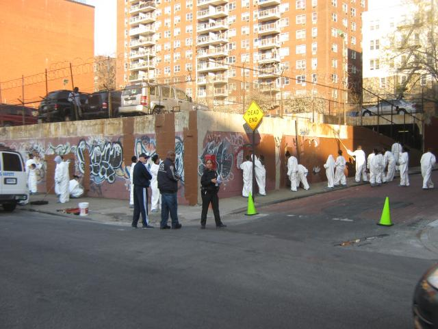 Adolescent diversion program participants from Bronx Community Solutions work with NYPD officers to remove graffiti in the 46th precinct. The adolescent diversion program is a new pilot initiative in the New York State Court System that works to improve the judicial response to 16- and 17-year-old offenders. (May 2, 2012)