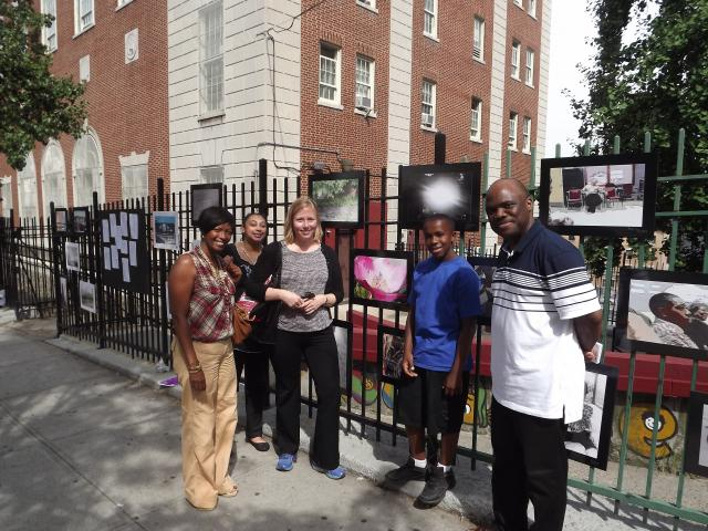 At National Night Out 2012, staff from Bronx Community Solutions, a local pastor, and a young artist, pose in front of photographs by local members of a community program that engages youth in arts-related projects. (August 8, 2012)