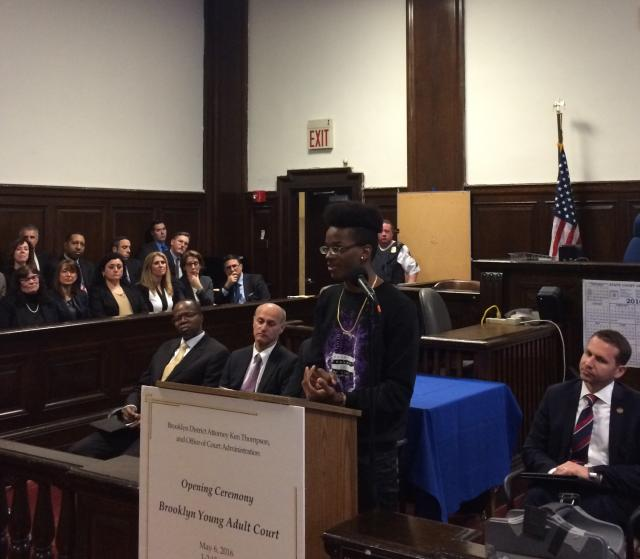 Brownsville Community Justice Center youth participant Ray speaks about his experiences at the Justice Center during the inauguration of the Brooklyn Young Adult Initiative at Brooklyn Criminal Court. Behind, Brooklyn District Attorney Kenneth Thompson (left), New York State Chief Administrative Judge Lawrence Marks (center), and Brent Cohen of the U.S. Department of Justice Office of Justice Programs (far right) look on.
