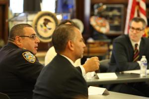 Captain Joseph M. Gulotta of the 73rd Precinct speaks at the roundtable. In foreground is James Brodick, director of the Brownsville Community Justice Center. In background is Thomas Abt, the chief of staff of the Department of Justice's Office of Justice Programs.