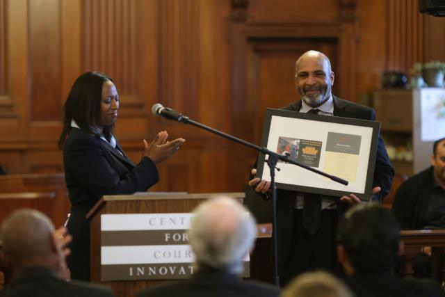 Bronx Community Solutions Director Maria Almonte-Weston honors Community Service Supervisor Ramon Semorile at the program's 10th anniversary celebration. (April 22, 2015)
