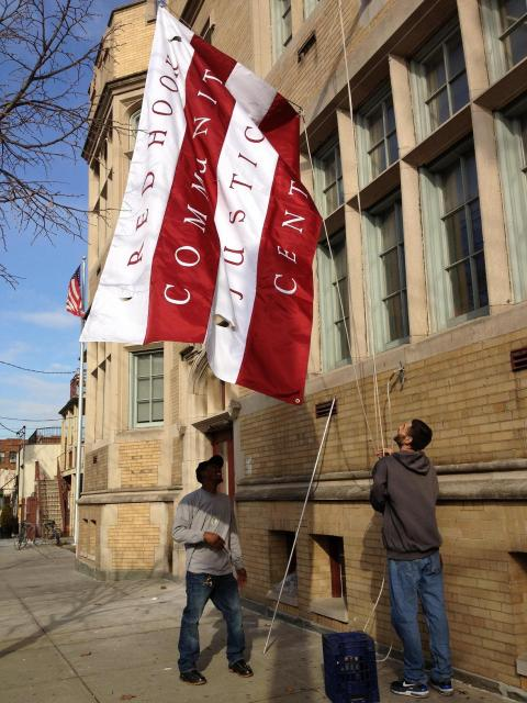 A new flag goes up the Red Hook Community Justice Center, replacing the one damaged by Hurricane Sandy. (November 28, 2012)