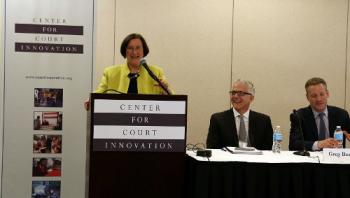 Bureau of Justice Assistance Director Denise O'Donnell delivers her keynote remarks while Center for Court Innovation Director Greg Berman (far right) and Director of Training and Technical Assistance Julius Lang look on.