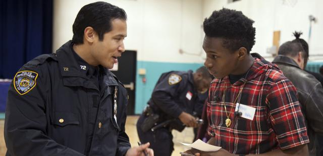 As part of our focus on enhancing trust in justice, the  Red Hook Community Justice Center recently hosted its third 'Bridging the Gap' event. The series brings together local police, young people, and community members to facilitate conversation and break down stereotypes. The theme of this event was 'Game Night,' and was attended by more than 100 people, including about 25 officers. Seen here is Officer Fuentes of the  72nd Precinct in conversation with one of the evening's participants. Click  here for more information on the evening. (Picture by Lauren Henschel.)