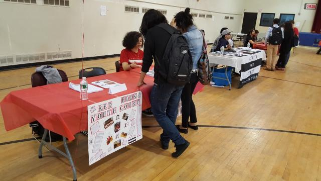 Red Hook Community Justice Center Youth Court Member Alanis Lantigua runs the youth programs table at the Justice Center's Youth Summer Internship and Jobs Fair. (May 13, 2015)