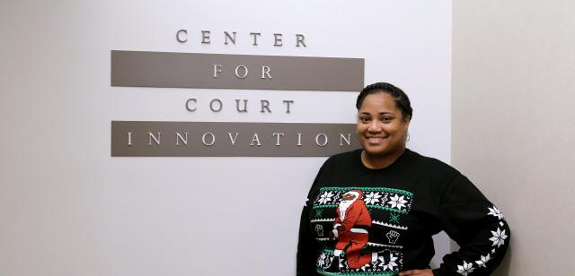 "Renowned rapper and Queens-native Nas is selling a line of ""Kneeling Santa"" sweaters this holiday season, here modeled by Sharese Crouther, Strategic Partnership Specialist at our headquarters in Manhattan. A portion of the proceeds from every sweater sold helps fund our work. To make your holiday a little more hip-hop—and, yes, they offer priority shipping—click here."