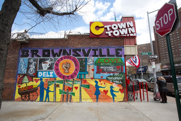 Volunteers partner with a community arts coalition to create a mural on Belmont Avenue.