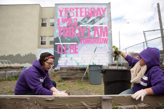 Planting new trees in a community garden in the shade of a mural created by Groundswell in collaboration with the Brownsville Community Justice Center.