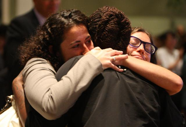 Nicolet Robinson, honoree and former client, gets a hug from her Legal Aid lawyer Kate Mogulescu, left, and Coordinator of Trafficking Programs at the Center for Court Innovation Miriam Goodman.