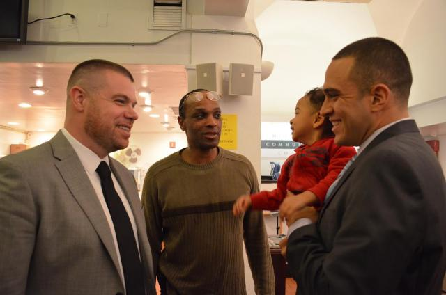 At Midtown Community Court's Serving Fathers, Strengthening Families celebration, Times Square Ink/Dads United for Parenting graduate Willie Key (center) speaks with program coordinators Bo Twiggs (left) and Jonathan Monsalve (right, holding Mr. Key's son). (November 21, 2012)