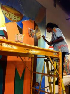Youth working on the Justice Center's Youth Justice Programs room mural, in collaboration with Groundswell