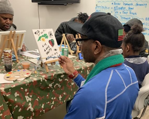 A man paints a canvas; a healing space of the arts with the RISE Project