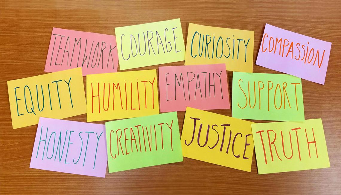 Inspiring words like courage, justice, empathy, on colorful sticky notes.
