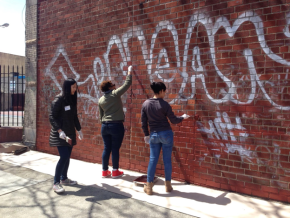 Community youth work together to remove graffiti.
